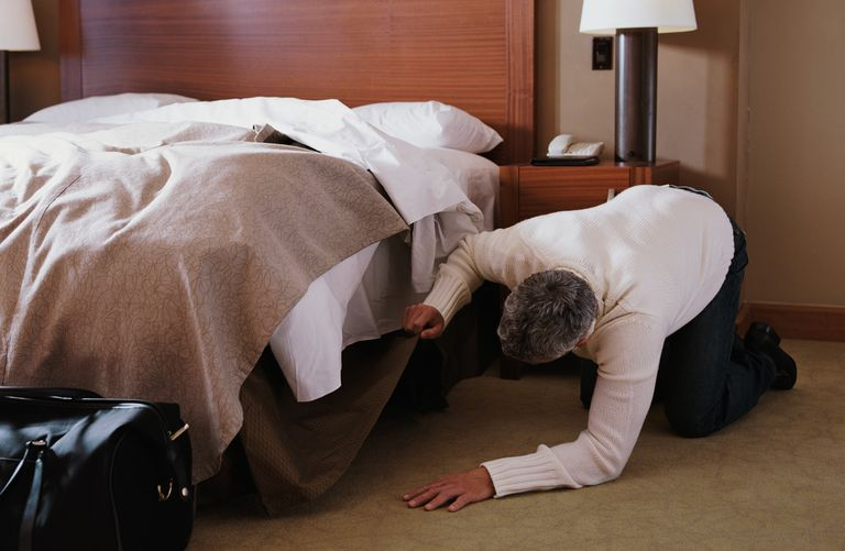 a man checks under his bed to see if a body is there - one of the classic las vegas urban legends