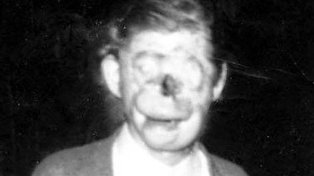 a blurry picture seemingly of a man with a distorted face or no face - urban legend
