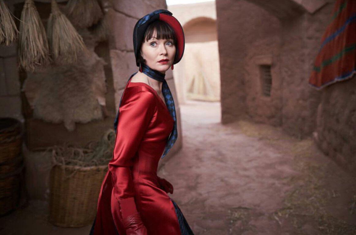 Miss Fisher looks over her shoulder in a desert bazaar in Miss Fisher & The Crypt of Tears
