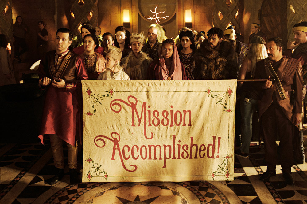 Cast of the Magicians stands with a mission accomplished sign