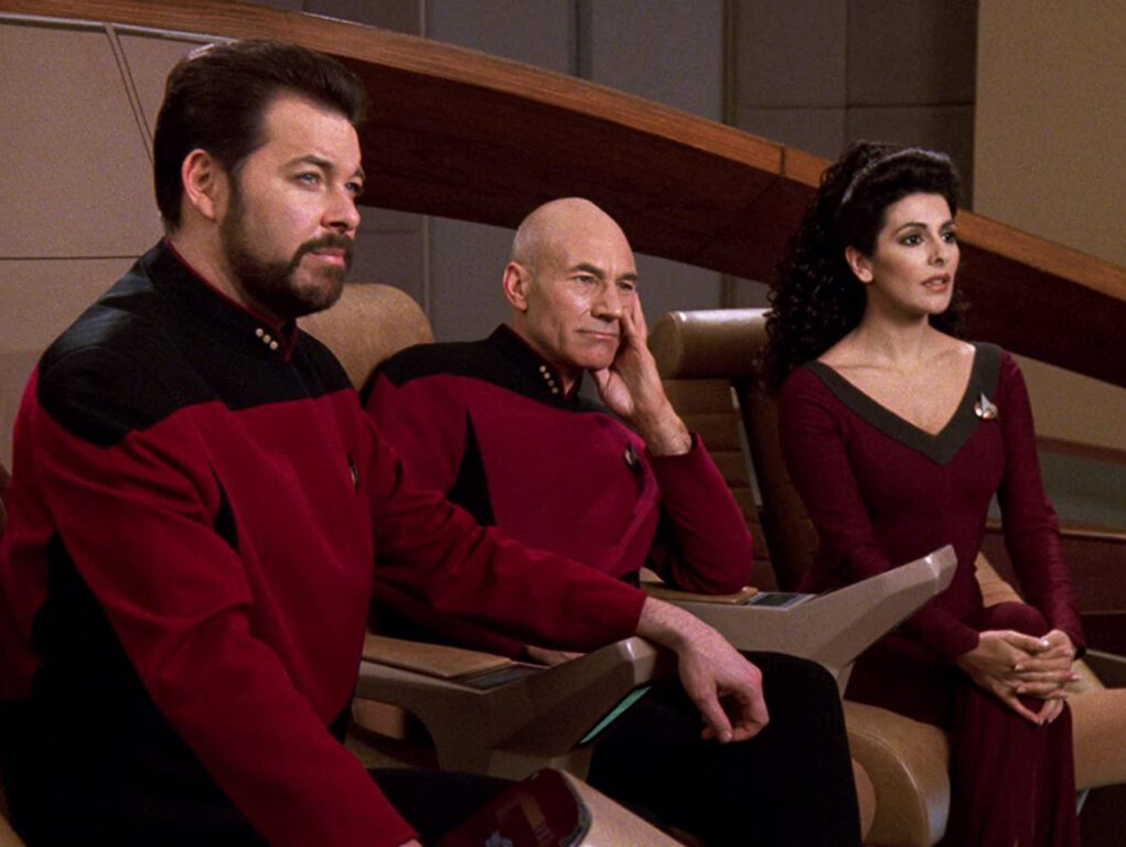 "Jonathan Frakes as Commander Riker, Sir Patrick Stewart as Captain Picard, and Marina Sirtis as Counselor Deanna Troi in the episode ""I Borg"" (s5e23) of Star Trek: The Next Generation"