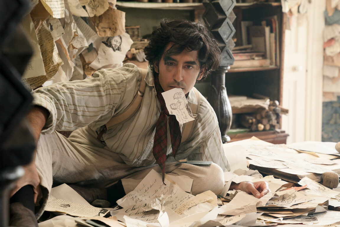 Dev Patel surrounded by paper in The Personal History of David Copperfield