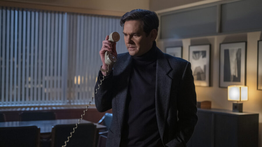Henry Wingrave, portrayed by Henry Thomas, answering the phone in his office in The Haunting of Bly Manor.