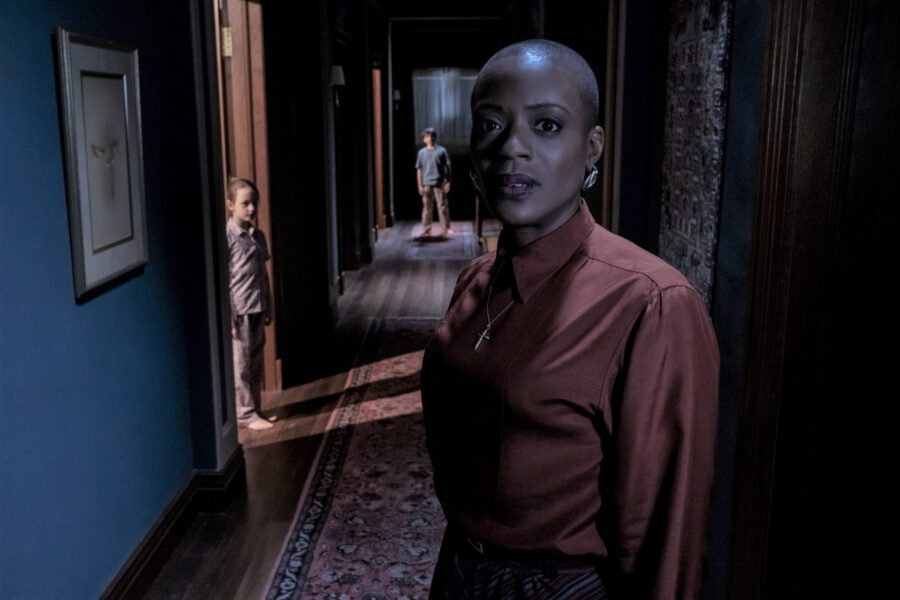 Hannah Grose, portrayed by TNia Miller, standing in the hallway with Flora and Miles in the Haunting of Bly Manor.