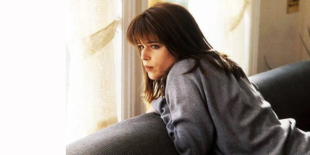 Neve Campbell as Sidney Prescott looking out a window in Scream.
