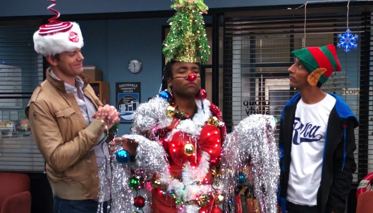 Still of Joel McHale, Donald Glover and Danny Pudi looking festive in Community.