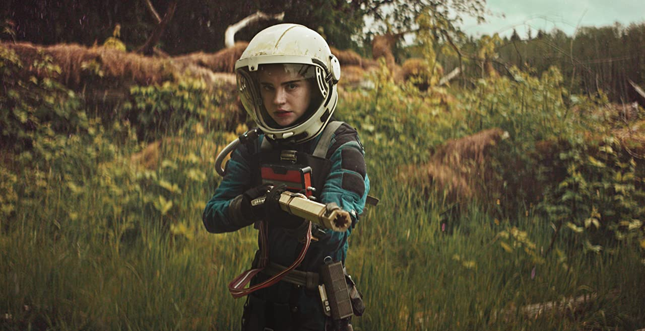 Actress Sophie Thatcher dressed in a blue, black, and white space-suit holding a gun in a scene from the 2018 movie Prospect.