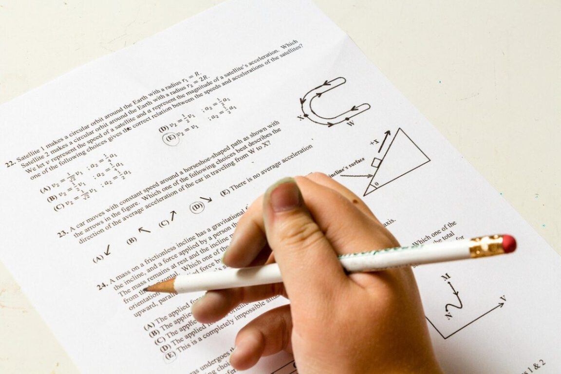 hand holding pencil over test paper