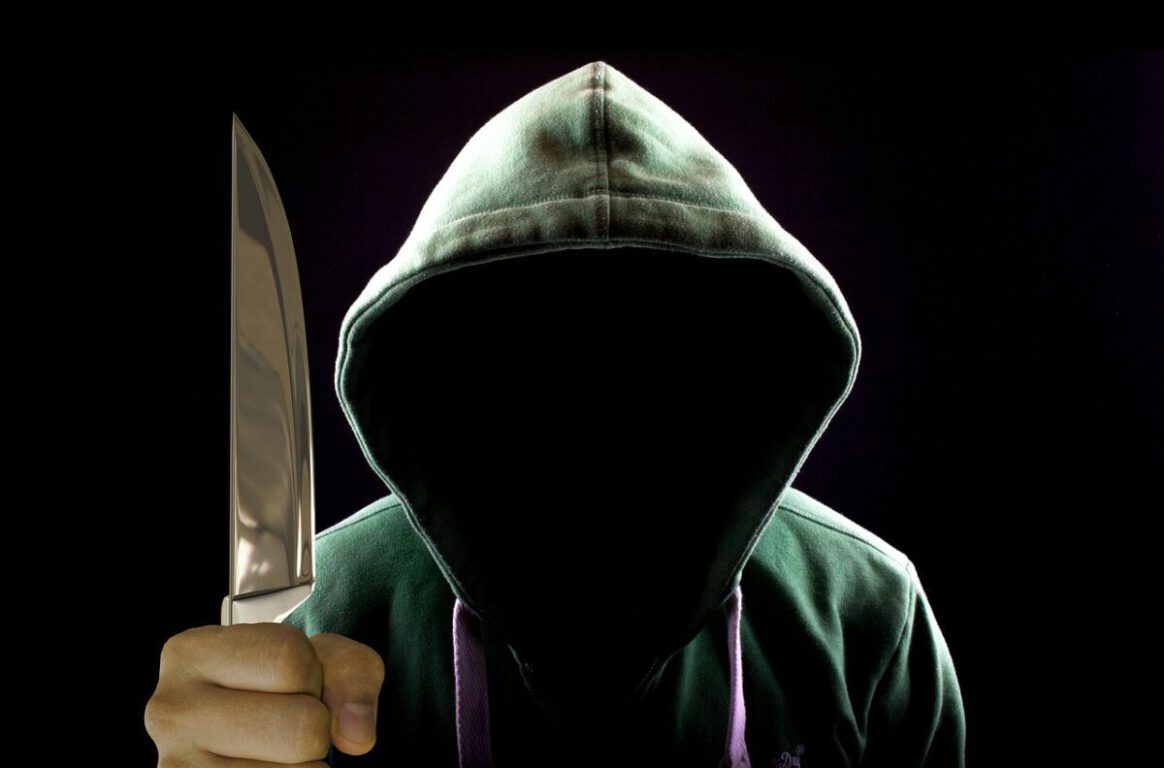 Faceless person holding a knife