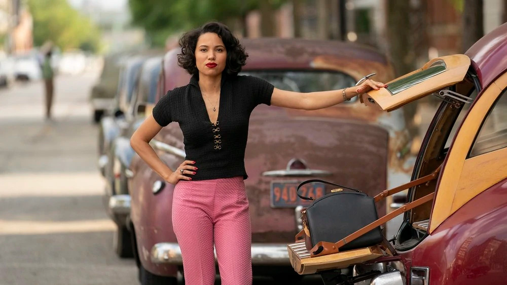"""Letitia """"Leti"""" Lewis (Jurnee Smollett-Bell) standing next to the car woody in Lovecraft Country."""
