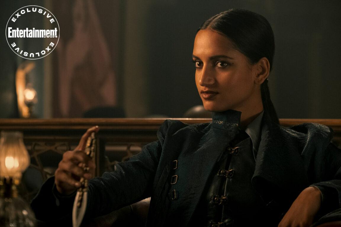 Inej Ghafa (Amita Suman) sitting back and playing with a knife in Shadow and Bone.