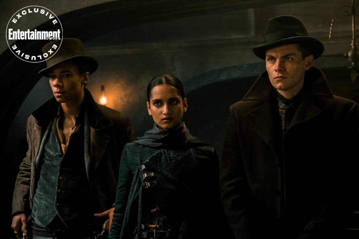 The Six Crows gang with Jesper Fahey (Kit Young), Inej (Amita Suman) and Kaz Brekker (Freddy Carter) standing together in Shadow and Bone.