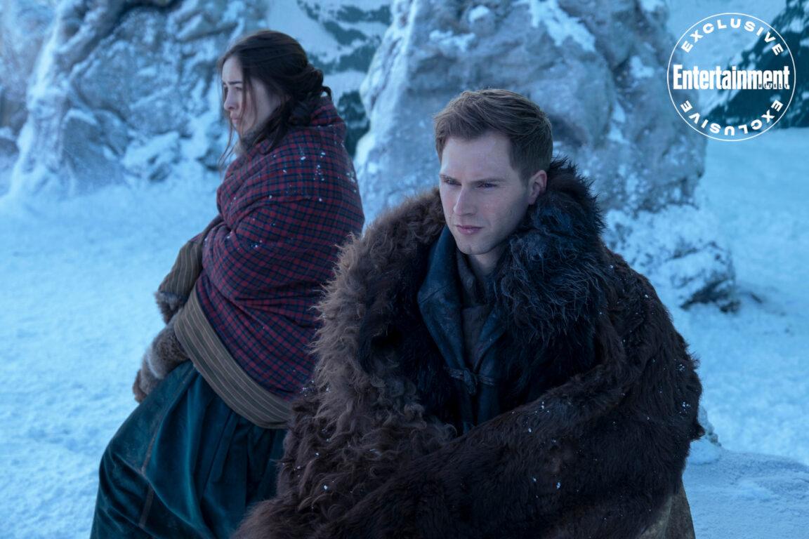 Nina Zenik (Danielle Galligan) and Matthias Helvar (Calahan Skogman) sitting together in the snow in Shadow and Bone.