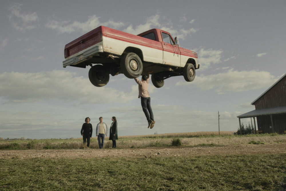 Clark Kent lifting his trucking above his head in front of his kids.