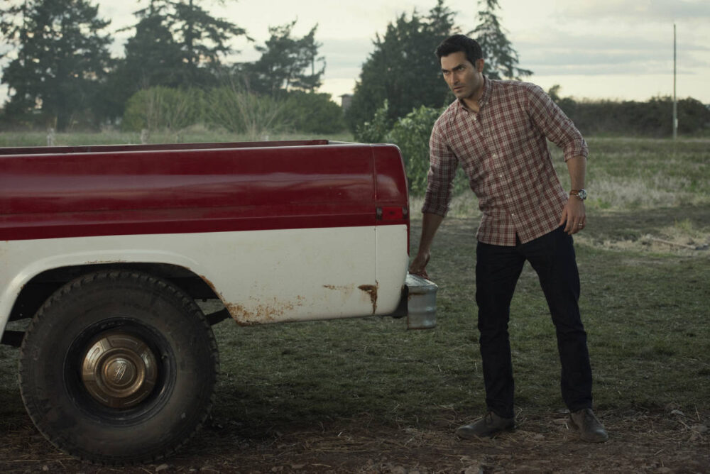 Clark Kent standing at the back end of his truck.