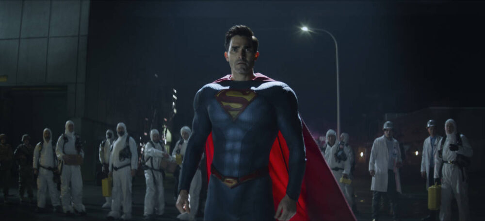 Superman standing in front of a group of scientists and workers.