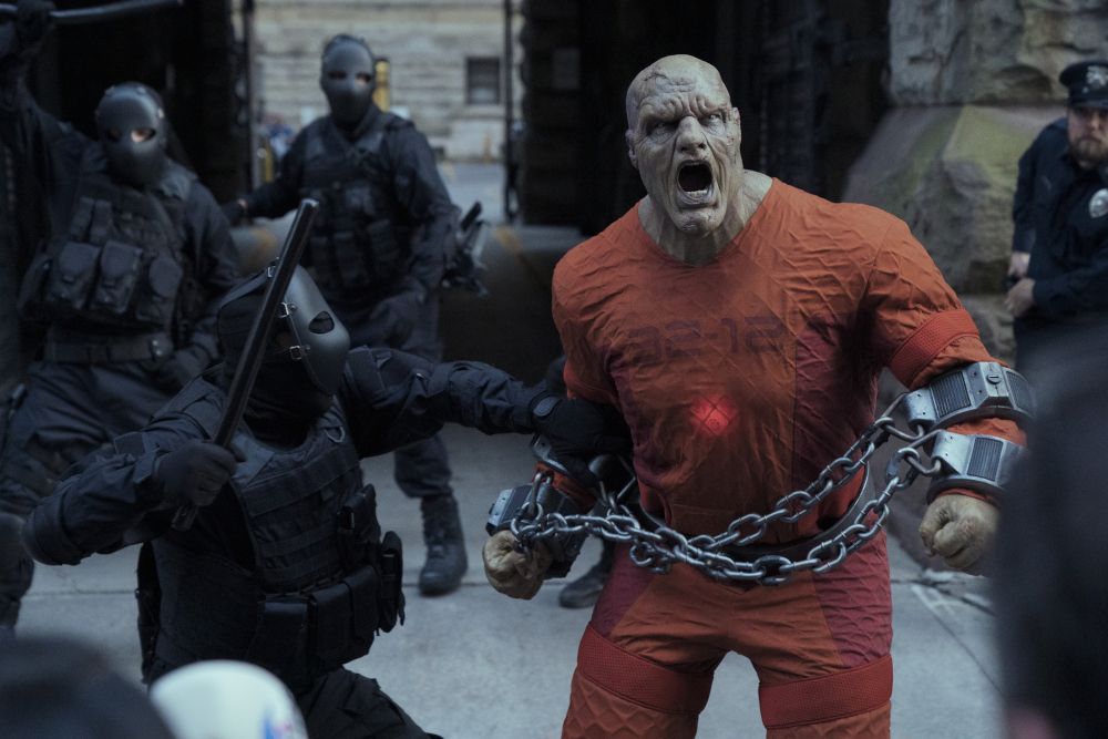 TYLER MANE as BLACKSTAR in cuffs surrounded by armed guards.