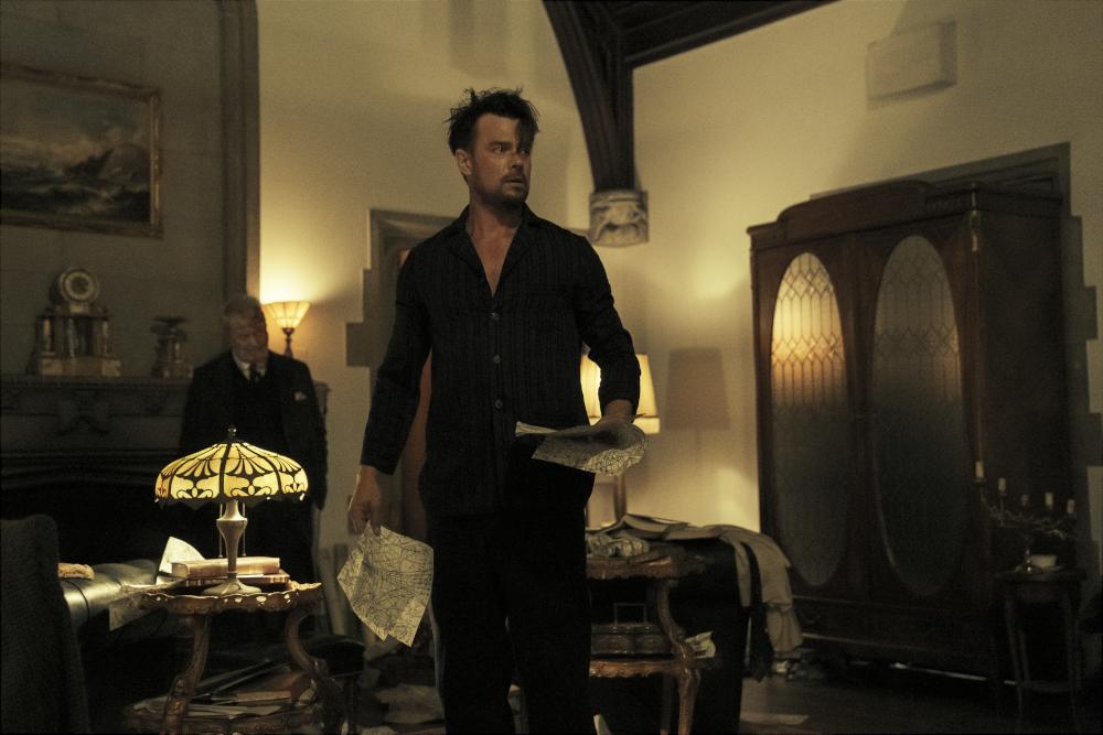 JOSH DUHAMEL as SHELDON SAMPSON standing in a study in his home.