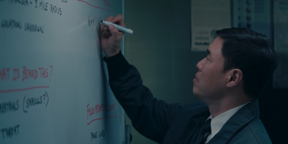 Jimmy Woo writing his theories on a whiteboard.
