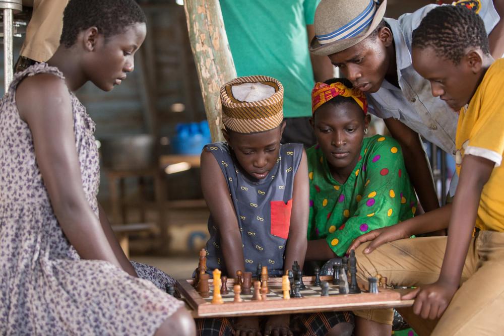Madina Nalwanga as Phiona Mutesi playing chess with her friends in Queen of Katwe.