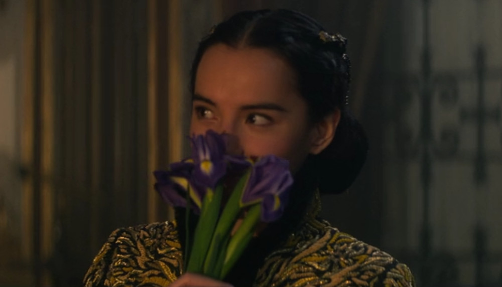 Alina sniffing the flowers Kirigan gave her in Shadow and Bone.