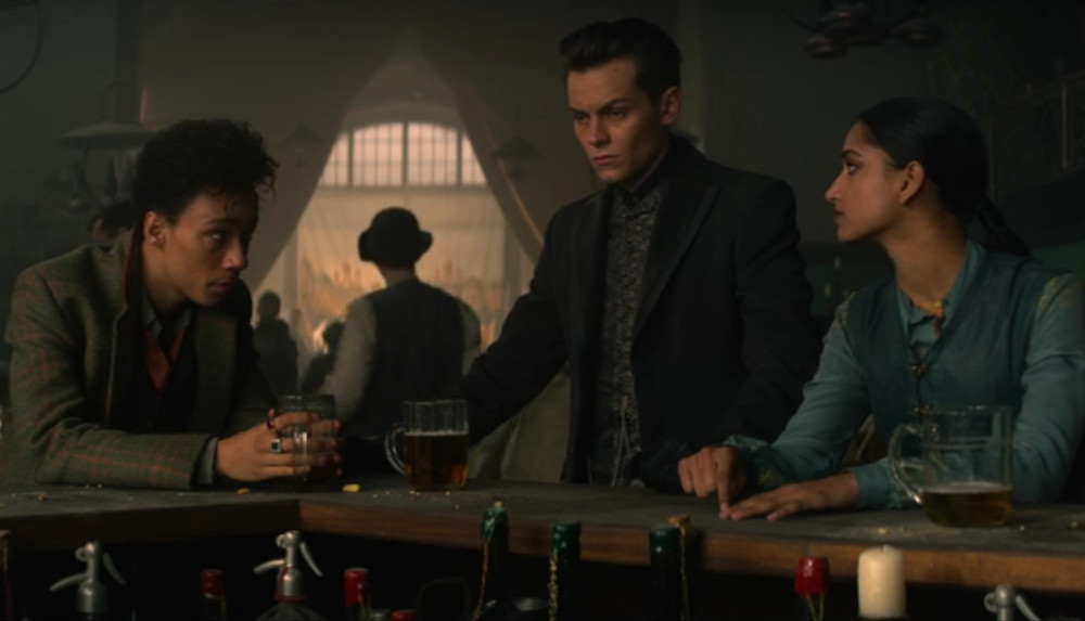 Jesper, Kaz and Inej trying to figure out how to break into the Little Palace in Shadow and Bone.