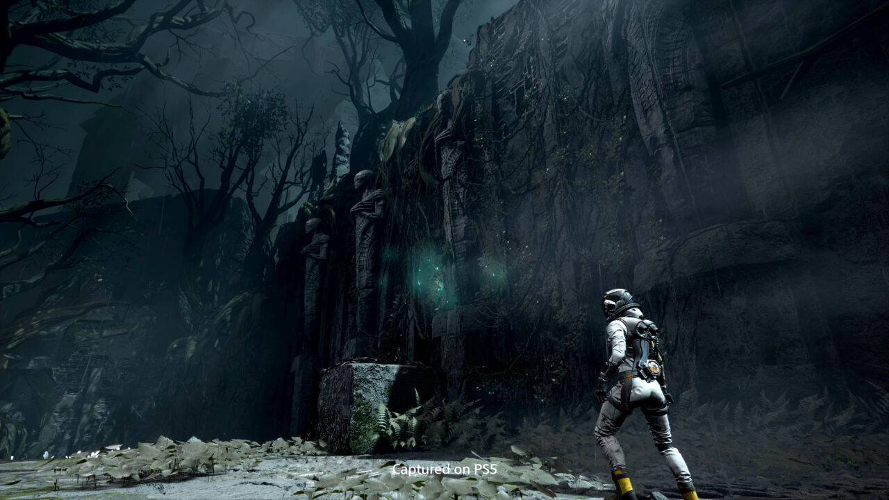 Returnal shot of the player outside a mysterious and dark building.