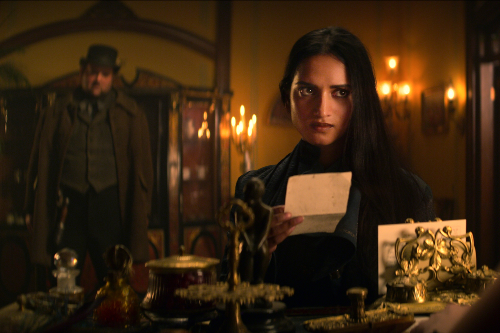 Amita Suman looking over a paper with an ominous man in the background.