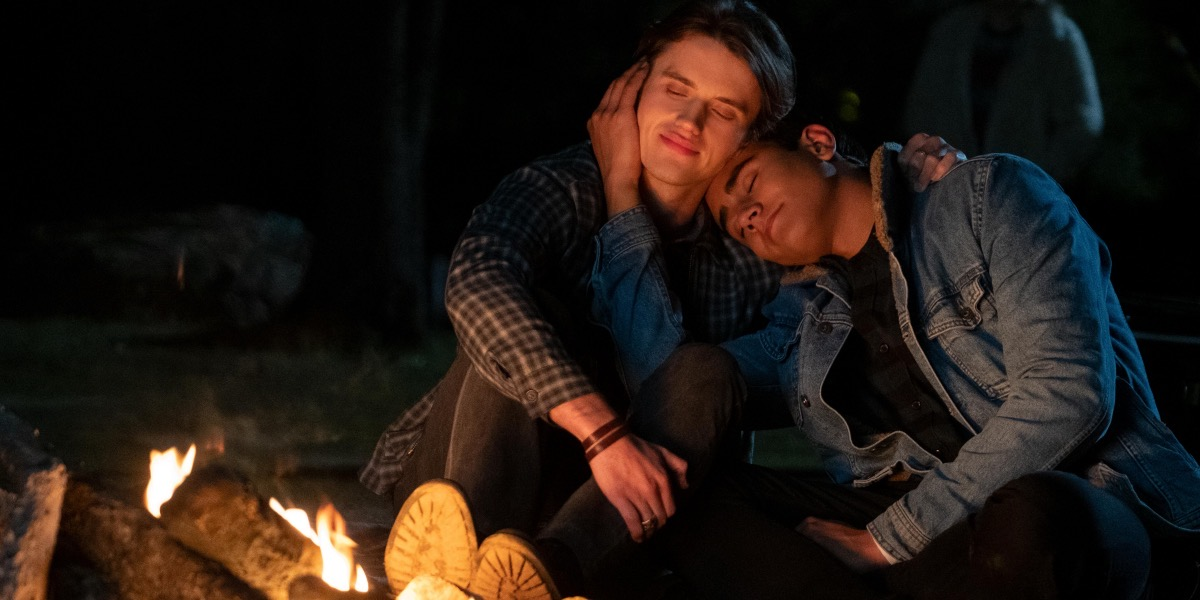 Benji and Victor cuddle by the campfire