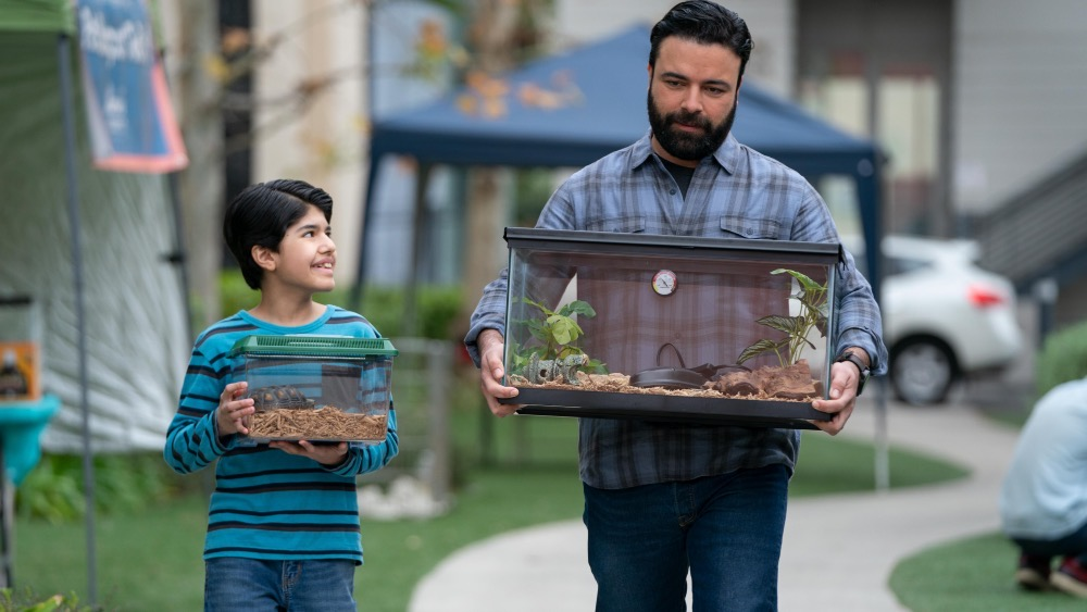 Adrian and Armando walk with a turtle and cage