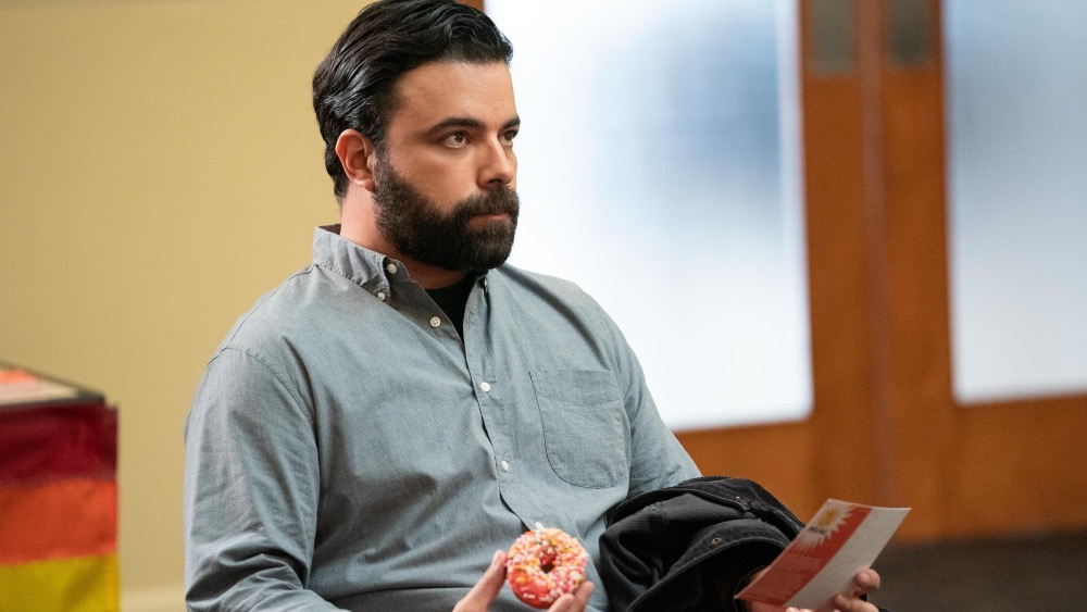 Mando sits at a PFLAG meeting, with a donut in his hand